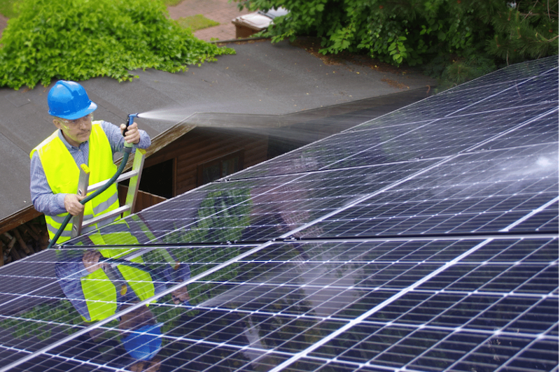 A solar energy technician cleaning solar panel with water only