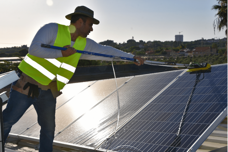 A solar energy technician cleaning solar panel with water